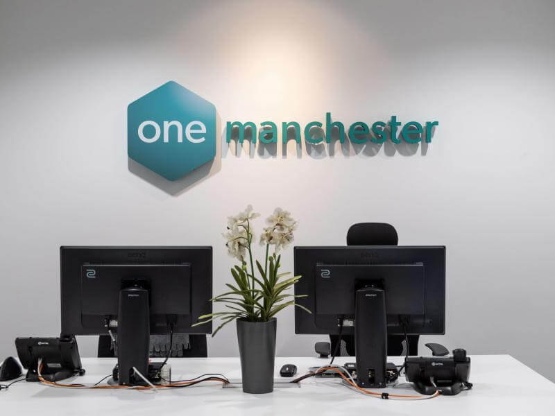 Desk with One Manchester logo
